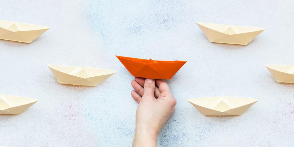 Vários barquinhos de papel iguais. Um barquinho de papel laranja ao centro sendo escolhido.